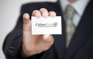 man holds printed business card